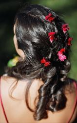 down bride hairstyle with big curls and red flowers.jpg