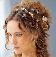 curly wedding half updo hairstyle with small flowers clips with side bangs