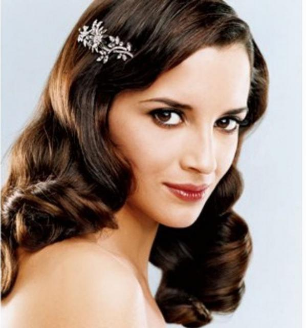 Photo of wavy down bride hairstyle w/ crystal hair clip