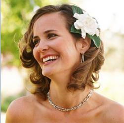 Mature bride hairstyle with light curls with long side bangs and big floral hair clip.JPG