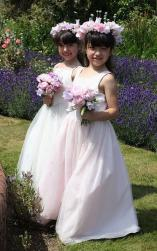 Flower girls in light pink wearing big flower headbands with pink flowers.JPG