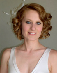Classic curly bob bridal hairstyle with side bangs and feather hair clip.PNG
