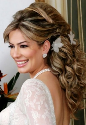 Big curly wedding hairstyle with full curls and straight side bangs and floral hairclips