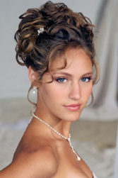 Classic curly wedding updo with curly side bangs and small flower hairclip