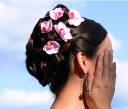 Brunette curly bridal hairstyle with small pink fresh flowers.PNG