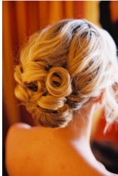 Lower wedding updo with rolls and long side bangs.PNG