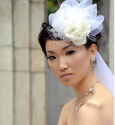 Stylish asian bridal updo with big rose hairclip with veil.PNG