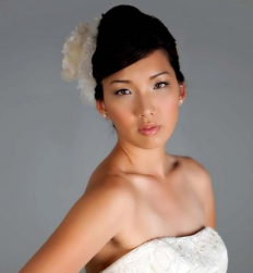 2010 Asian bride updo with big floral hairclilp and side bang.PNG