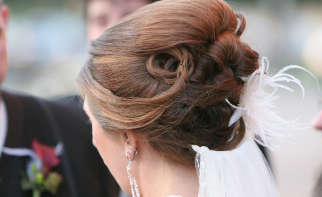 Classic bridal hairstyle with feather hair clip and veil.PNG