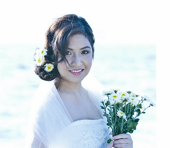 Side bride updo hairstyle with daisy flowers and long bangs.PNG