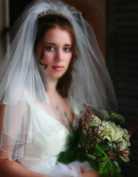 Curly bridal hairstyle with long curly side bangs with terria and veil photo.PNG