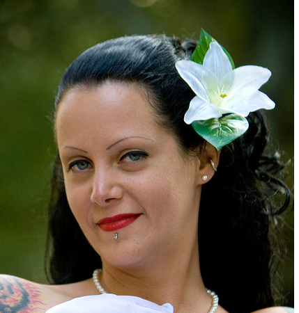 Down wedding hairstyle with big white floral hairclip on the side.PNG