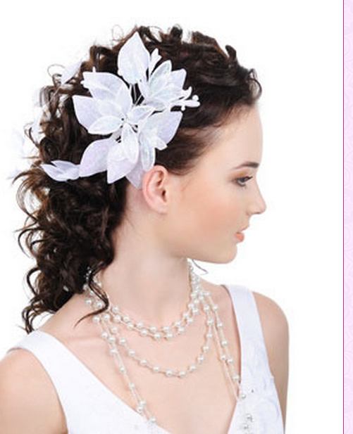 Curly wedding hairstyle with a big white floral hairclip.PNG