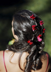 Down wedding do with curls and red fresh flowers as hairclips.PNG