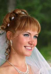 Pretty wedding updo hairstyle with veil and small flowers.PNG