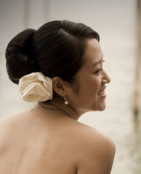 Simple Asian brides hairstyle with white rose hairclip on the lower right back side.PNG