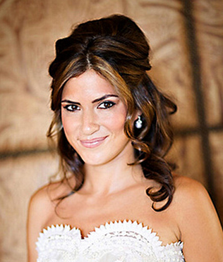 Trendy bridal hairstyle with half up with full of wavies and curls and long side bangs.PNG