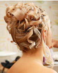 Rolls and curly bridal hairdo with straight hair in the front.PNG