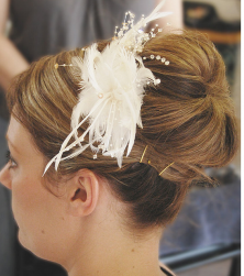 Big wedding hairdo with rolls in the back and feather hairclilp pictures.PNG